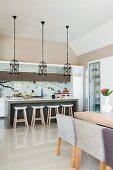 Dining set in front of counter and bar stools below row of pendant lamps with bird-cage lampshades