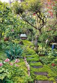 Stepping stone path through flowering garden leading to idyllic seating area
