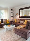 Corner sofa with brown cover and white coffee table on Berber rug in traditional living room