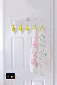 DIY pegs made from rolling pins on interior door