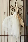 White tutu with wings hung on artistic wrought iron lattice
