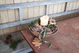 Pine cones, stag ornaments and pillar candle arranged in bowl
