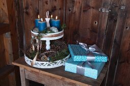 Elegantly wrapped gifts and Advent arrangement on vintage-style cake stand against wooden wall