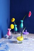 Glass vessels decorated with pastel balloon rubber and single flowers against royal blue walls