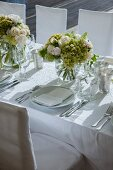 Bouquets of white roses on festively set wedding dinner table with white tablecloth