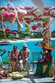 Luxuriant floral decorations for Indian beach wedding beneath a blue sky
