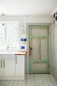 Vintage back door next to white kitchen counter below window