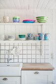 Crockery on bracket shelves above kitchen counter and white-tiled splashback