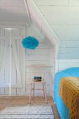 White, wood-clad attic bedroom with pink-painted chair below blue pompom suspended from ceiling