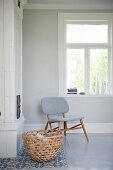 Chair with pale grey upholstery below window in corner behind wicker basket of firewood next to fireplace
