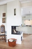 Modern fireplace in partition wall with country-house kitchen in background