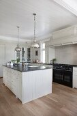 Island counter and silver pendant lamps in country-house kitchen
