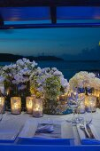 Wedding dinner table festively set with candle lanterns and bouquets at twilight