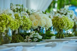 Glass vases of various flowers on wedding dinner table