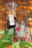 Karaffe mit gebasteltem Etikett und Gläser mit Kirschen