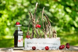 Twigs stuck in brick decorated with writing and cherries