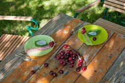 Gartentisch mit grünen Tellern und Kirschen