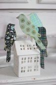 DIY Vogelstecker aus Buntpapier und Wellpappe in die Fenster eines Lichterhäuschens gesteckt