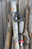 Gebundenes Herz und Reisigkranz mit Fliegenpilzdeko an angelehnten Holzstämmen