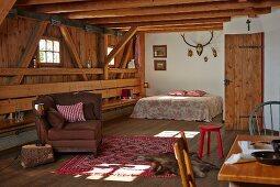 Offener Wohnraum mit Sitzmöbeln und Doppelbett in ländlichem Holzhaus