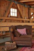 Brauner Polstersessel mit Überecklehne und Leuchte auf Baumstamm-Tisch, dahinter Holzwand mit offener Balkenkonstruktion