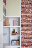White, custom-made corner shelving with open compartments and cupboards adjoining unrendered brick wall