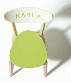 Holzstuhl aufgepeppt mit grün gemalter Sitzfläche und Schriftzug