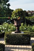 Planted classic urn on plinth surrounded by box hedge in sunny garden