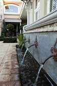 Vintage-style water spouts and stream running along façade of elegant country house