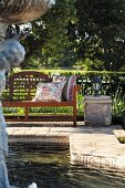 Garden bench with cushions in the sun next to pond