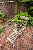 Wooden sun lounger in corner of rustic garden with wooden decking, gravel area and brick-paved terrace
