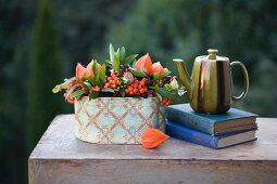 Autumn still-life arrangement of berries, teapot and old books