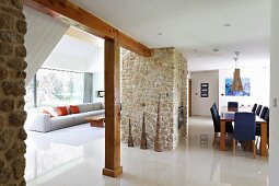 Open-plan interior with pale polished stone floor, lounge area, dining area with central fireplace in stone chimney breast