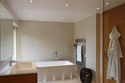 Bathtub lit by recessed floor lights against tiled wall and recessed spotlights in suspended ceiling in elegant modern bathroom
