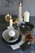 Decorative china bowls, silver owl and hand-painted gift labels in front of lit candles