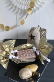 Christmas present wrapped in gold paper and gold-painted pebbles