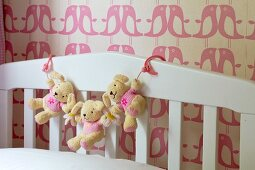 Garland of teddy bears on white cot against bird-patterned wallpaper