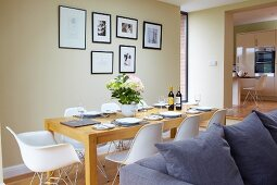 White classic shell chairs at set table in open-plan interior with walls painted pastel green