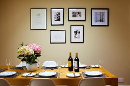 Wine bottles and hydrangea on set dining table in front of framed pictures on pastel wall