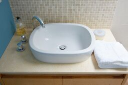Washstand with countertop sink and pale beige mosaic-tiled splashback