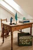 Stacked books and comic figurine on vintage wooden table above printed wooden crate in attic room