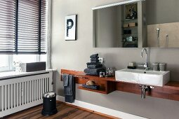 Custom washstand with china countertop sink below mirrors on pale grey wall