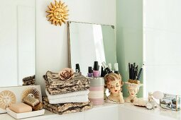 Stacked towels and makeup utensils on shelf with vintage accessories