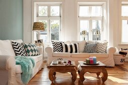 Scatter cushions with graphic patterns on sofas around two opium tables
