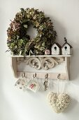 Wreath and vintage-style miniature nesting boxes on antique key rack with rose-patterned cups and love-heart pendant hanging from hooks