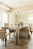Elegant upholstered chairs around solid-wood table below chandelier in dining room in shades of cream