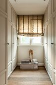 Roman blind on window in narrow dressing room with white, country-house-style wardrobes