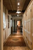 Pale, wooden custom cupboards and modern spotlights on wood-beamed ceiling in hallway