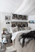 Bed with canopy and fur blanket in cosy bedroom