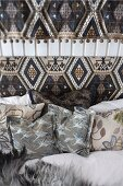 Scatter cushions on bed with patterned headboard